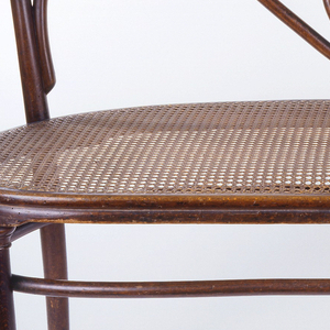 Settee with curved bent beachwood elements: the back composed of a wide frame enclosing two horizontal scrolling elements with an oval element in the lower center; single scrolled arm at either side with narrow, flat armrest at top; the wide caned seat on four tapering legs, the two front legs slightly out-turned; oval stretcher joined to all four legs slightly below seat.
