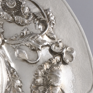 Circular dish with deep concave center.  Outer edge with seven chased lobes.  Wide flat border rises in curve toward center, chased with seven foliated poppy stems with seven blossoms, seven buds, four seed pods, three butterflies, and two flies, all in high relief.  Stems continue into recessed center as stylized swirls and lobes.  Textured hammered surface visible in all flat areas, smooth on central lobes.  Reverse of dish heavily patinated.