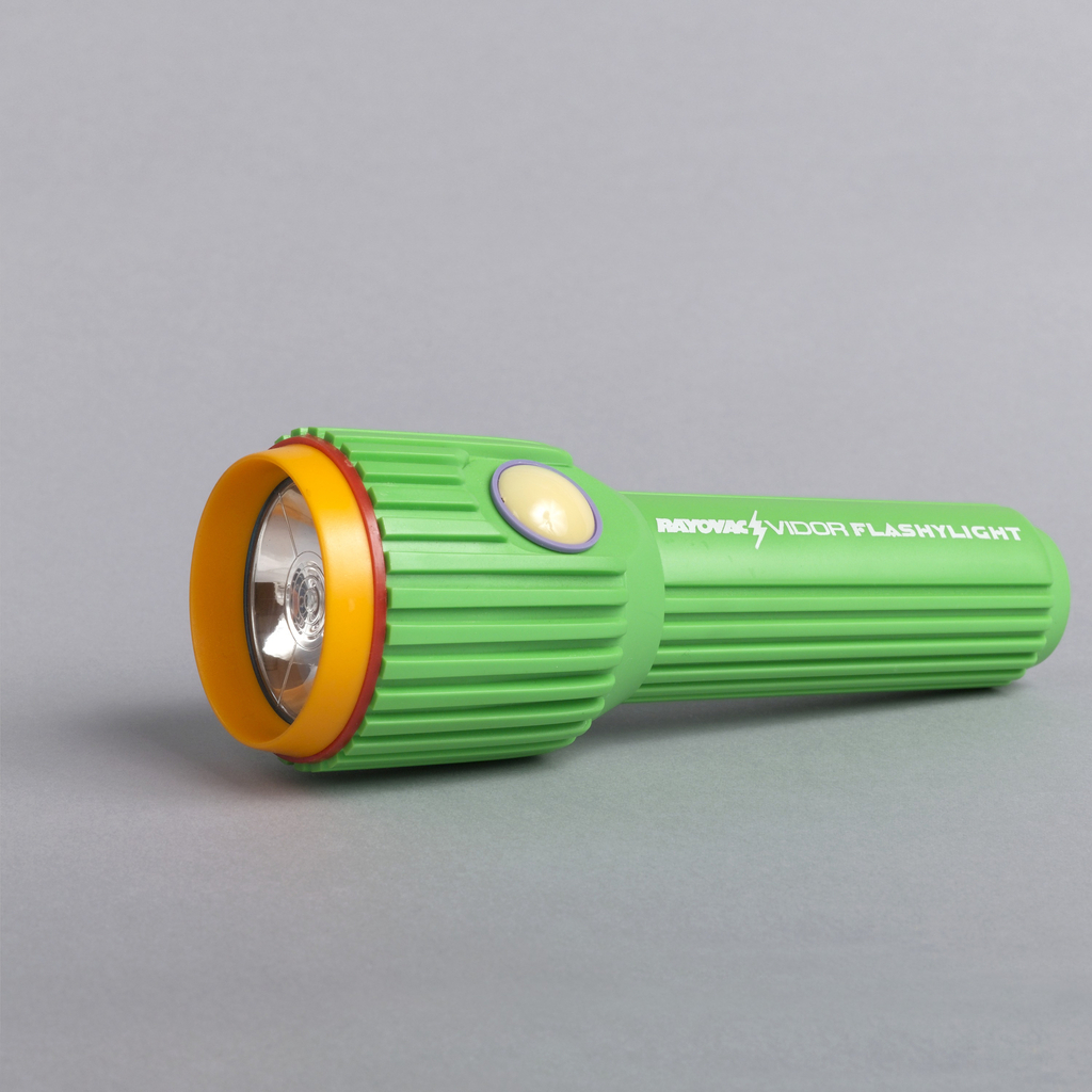 Lime green molded plastic form with high ridges lengthwise along cylindrical lamp housing and shaft; yellow and red plastic rings surrounding circular lens;  large white plastic hemispherical on/off button encircled by narrow lavender plastic ring.