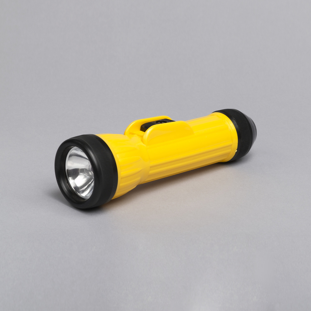 Yellow plastic molded body with threaded battery cap in black plastic at one end.  Cylindrical body ridged and flared out to form larger lens opening.  Lens and lamp held by black ridged plastic neck ring.