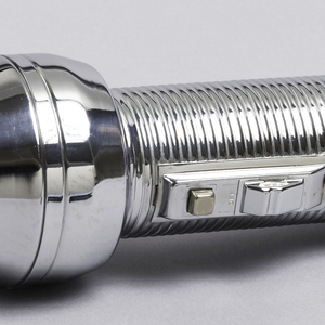 Molded chrome-plated cylindrical body with horizontal ridges.  Shaped lens cover and attached suspension ring at end.