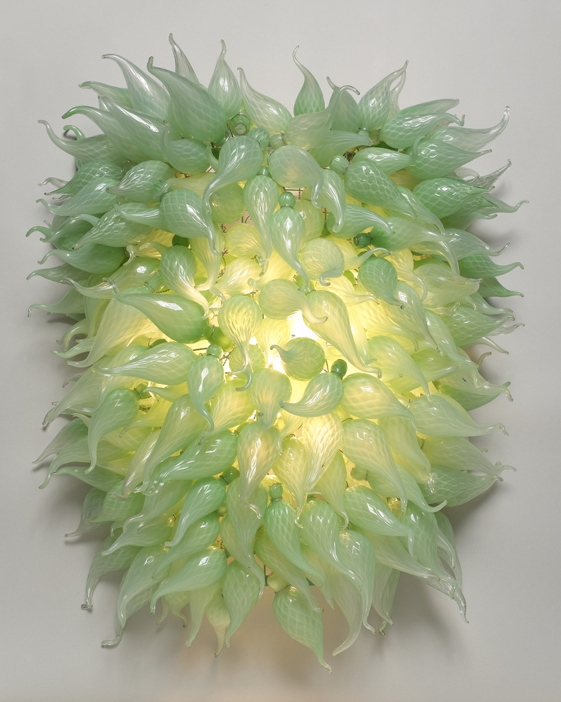 Green glass leaf-like three dimensional teardrop plant form covering light bulbs of sconce.