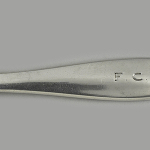 "Half-spherical base with thin disc on bottom; slightly curved paddle-shaped handle with indentation for thumb and finger and monogram ""FCR"", tapering near base."