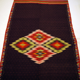 Late Classic Saltillo serape with a brown field and a central aggregate diamond. Brown field has a repeating red dot pattern with a white wavy dot stripe on either side. Warp ends have multicolored stripes and short off-white fringe. Side borders are stacked, variegated rhombuses in red, purple, yellow-green, dark blue, and light blue.