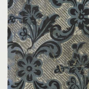 Vertical rectangle composed of pieced fragments. Repeating design of crossed foliate scrolls, black on blue, enclosing gray area with diagonally overprinted white stripes, in center of which is a floral spray in black on blue. Diaper or trellis-style design.