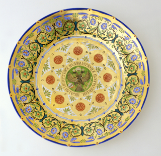 Circular form, the center decorated with black, double-headed imperial eagle on green ground within a circular band of Cyrillic lettering (translation: Nicholas the Emperor and Ruler of All the Russias), surrounded by decoration of red flowers in gilded lozenges alternating with green foliate forms; the rim with green and blue foliage intertwined with black scrollwork on gilded ground.