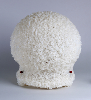 Malleable globular form with short base, the whole composed of milky-toned silicone string-like trailings; mounted on internal red plastic base housing light bulb and cord.