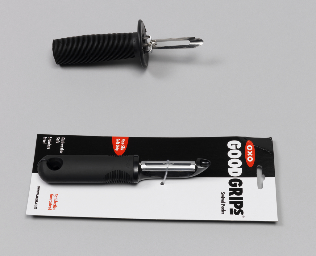 "Black hand peeler in packaging that reads: ""OXO / GOOD GRIPS / SWIVEL PEELER"". Peeler with syntetic rubber handle with grip consisting of horizontal striations, hole at bottom; swivelling stainless steel blade covered by clear plastic."