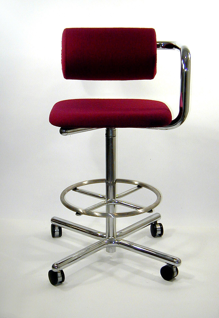 """Swivel stool on four legged rolling base.  Steel foot ring above splayed feet.  Square upholstered seat.  One tubular arm rises at  side, fitted with """"roll"""" support; this cylindrical arm or rest is adjustable in height or distance from seat by a ratchet system.  Upholstered in purple hopsack material."""