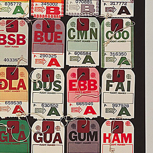 """On black ground, rows of airline luggage tags from airports around the world from ABJ (Abidjan, Ivory Coast), at upper left, to WAW (Warsaw), at lower right, arranged alphabetically.  Printed white text at bottom begins:  """"Airports are a link to the peace and places of the world. . ."""" and is followed by a key to the airport codes on the tags above. Printed white text at top lists the word for """"Airports"""" in various languages."""