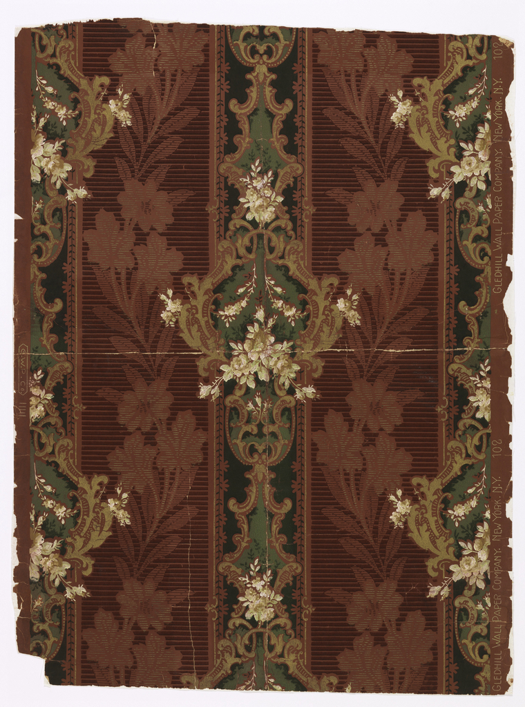 Alternating vertical stripes, the wider of which has serpentine ascending flowering branches. The other, narrower stripe is set with rococo scrollwork medallions in gold, and sprays of white flowers. Printed in gold, dark red, greens and white on red ground.