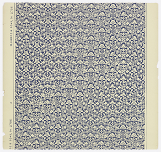 On cream ground, small-scale ogival pattern with stylized floral in-fills printed in blue.