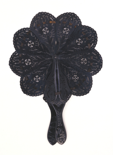 Brisé cockade fan. Sticks and guards are of black vulcanized rubber, drilled with an open design of delicate vines and flowers and a scalloped edge. Guards are attached to center of two outer sticks, all of which, threaded with ribbon. Spread to make a round form.