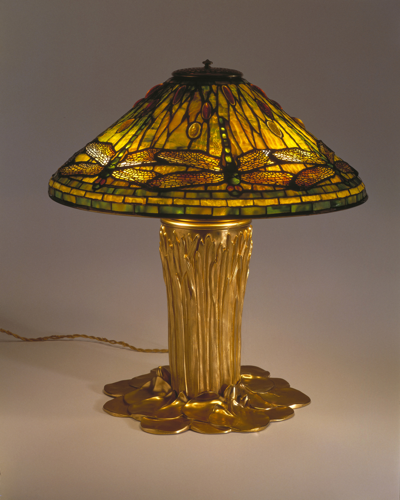 Conical shade of amber and green stained glass with dragonflies around the sides, on gilded base as bunch of tall grass surrounded by lily pads.