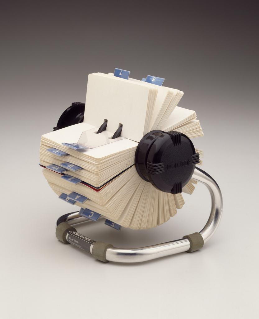 Free-standing rotary card file supported by single tubular metal element, bent to form U-shaped foot, with ends rising to terminate at opposite black plastic terminal knobs. Foot with four gray rubber cuffs.