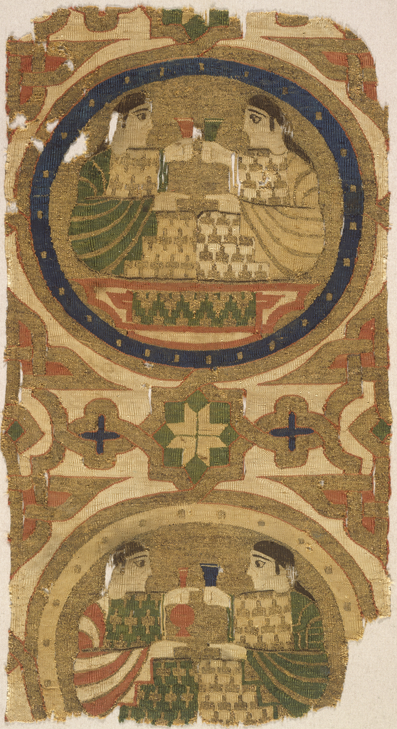 Fragment of woven silk containing one full and most of a second roundel, surrounded by interlaced bands forming star and rosette motifs. In the upper roundel, two confronted figures toast each other with cups raised; in the lower roundel the figure on the right raises a cup and the other figure a long-necked bottle. In dark blue, green, orange-red, and white on a gold metallic ground.