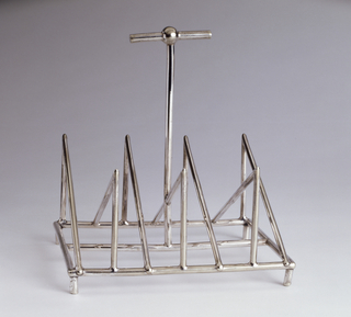 In the form of an openwork frame, the rectangular base set with seven alternating triangular supports along length of base; tall T-shaped handle rises from center; short peg foot at each corner of base.
