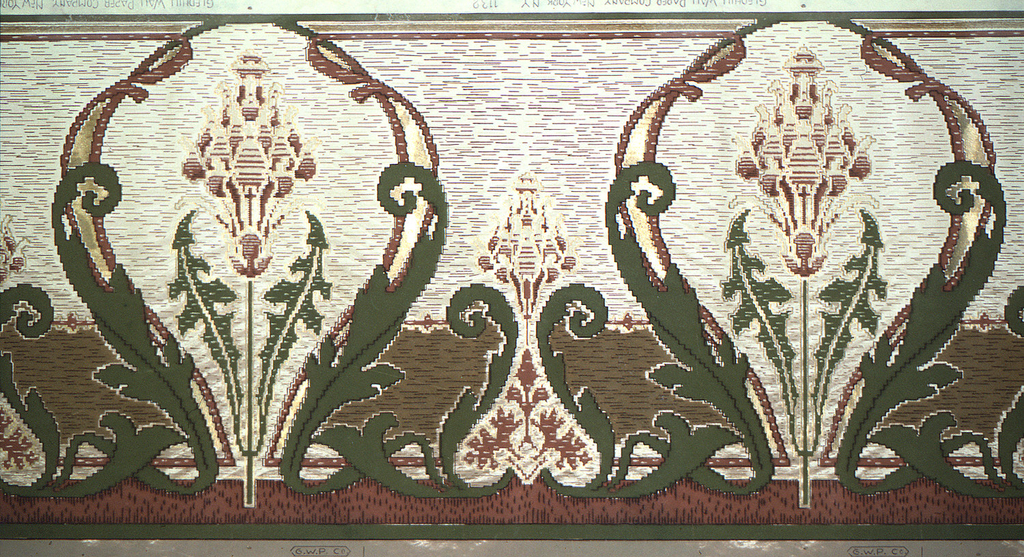 Art nouveau style. Stylized stemmed flowers, alternating beween large and small. The large flowers are encircled by swirling leafs. The base of the smaller flowers are also framed by curling leafs. The lines are jagged, giving the paper an embroided effect of The background consists of short, horizontal, brown and black lines. Printed in green, black, cream, and shades of brown.