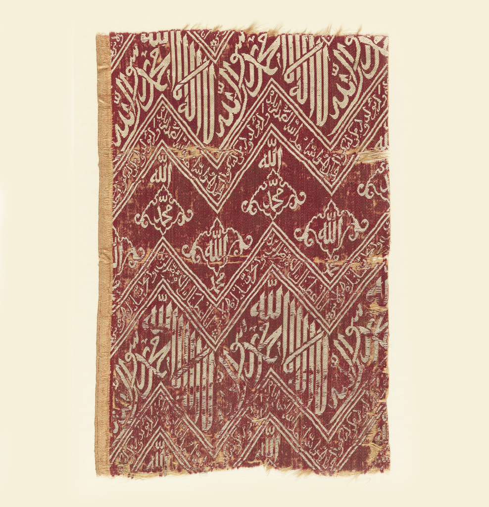 Fragment of woven silk with zigzag bands of Kufic script in white on a red ground. The inscriptions are translated as (top to bottom): 