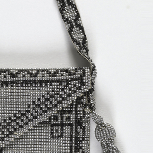 Small beaded bag, envelope shaped with flap and strap. Silver-colored beads form the ground, with design in black jet beads: an elephant on the back, and a rosette on the front, with borders of interlacing designs. With tassels at upper corners and bead fringe at bottom.