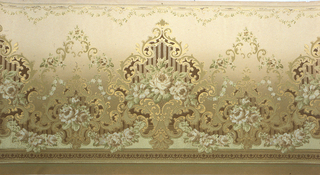 On cream-beige ground, scrolls and arabesques in gold with brown and pinkish-green and white roses.