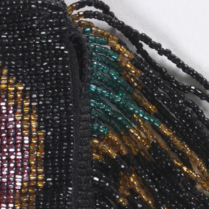 Green circle on one side of a black bag, red circle on the other, implying stop and go. Fringe each side, one worked in green, gold and black beads, the other worked in red, gold and black beads. Bag opens with snap fasteners to reveal a small pouch.