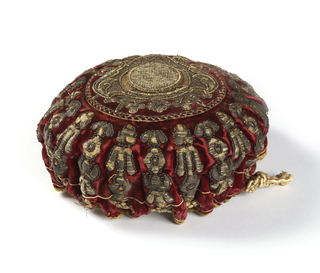 Purse of red velvet with silk drawstring. Embroidered with a coat of arms and conventionalized floral forms in metallic thread.