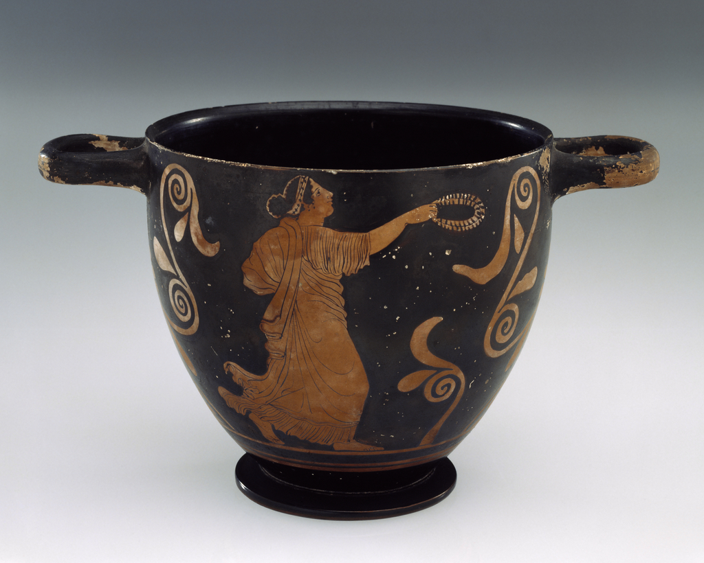 Tapering cylindrical form with two horizontal handles at rim, circular foot. Black and terracotta colored decoration consists of female figure dressed in chiton, running toward right with wreath in hand, and a nude youth seated on rock, facing right, staff in hand. Under the handles, symmetrical ornaments based on the palmette.