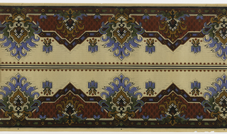 American Southwest Indian motifs. Borders printed two across (mirror). Alternating large and medium geometric, floral medallions connected by polygonal blocks with geometric patters. Top band has dentil pattern. Background of miniscule alternatng vertical dashes and dots. Paper is ungrounded. Printed in blue, dark yellow, dark reds, green, black and grey.