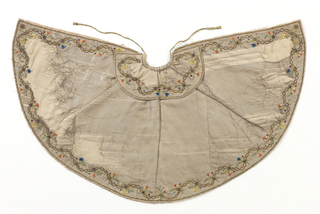 """Small cape for an ecclesiatic figure, the """"Bambino"""". Silver metal cloth with foundation of white silk. Small floral sprays of polychrome silk set into a winding chain of gold sequins and imiation amethysts. Lined with pink satin."""