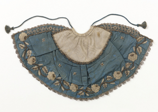 """Small cape for an ecclesiatic figure, the """"Bambino"""". Blue moire with silver moire collar. Edged with silver lace. Embroidered vine design along edge with gold cord and sequins and white glass beads. Lined with pale blue silk voile."""