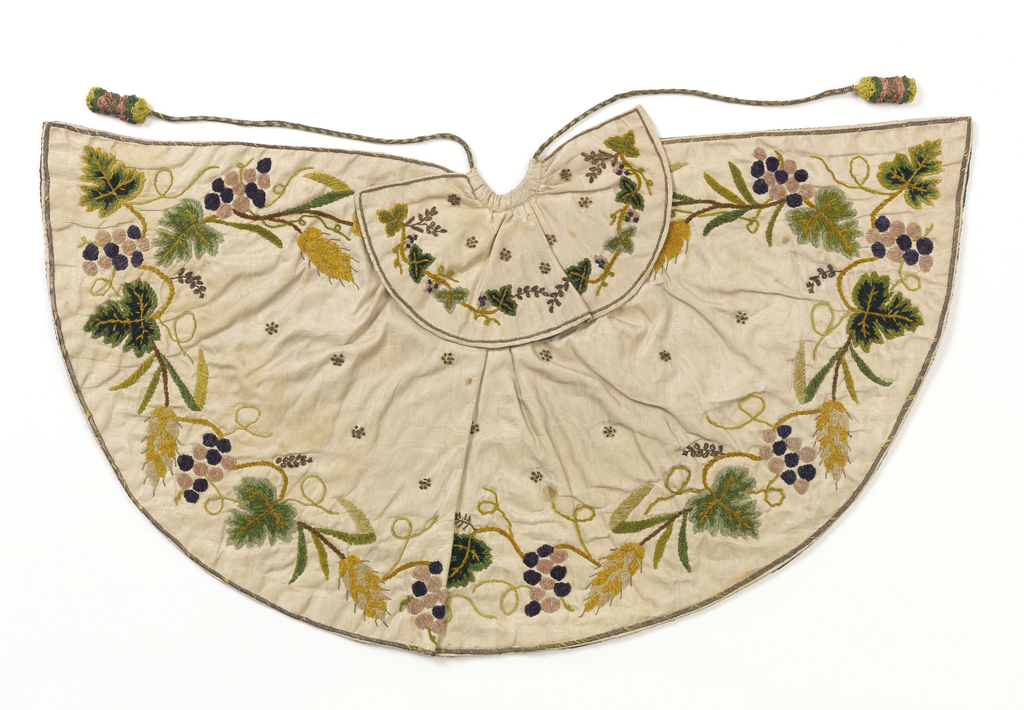 "Small cape for an ecclesiastical figure, the ""Bambino"". White silk moire embroidered with silk chenille in greens, yellows, purples, and gold sequins and thread. Grapevine and wheat design, large-scale, around edge of cape and on collar."