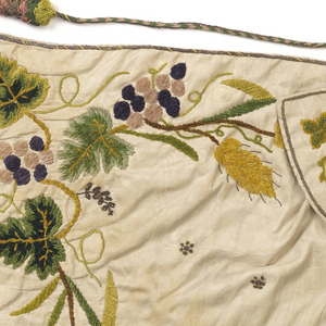 """Small cape for an ecclesiastical figure, the """"Bambino"""". White silk moire embroidered with silk chenille in greens, yellows, purples, and gold sequins and thread. Grapevine and wheat design, large-scale, around edge of cape and on collar."""