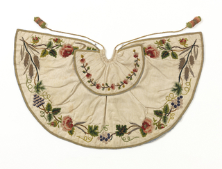 """Small cape for an ecclesiatic figure, the """"Bambino"""". White silk moire embroidered with silk chenille in greens, purples, rose, and gold sequins and gold and silver thread. Design of grapevine, rose and grain aroudn border. Lined with blue silk with white brocaded floral design."""