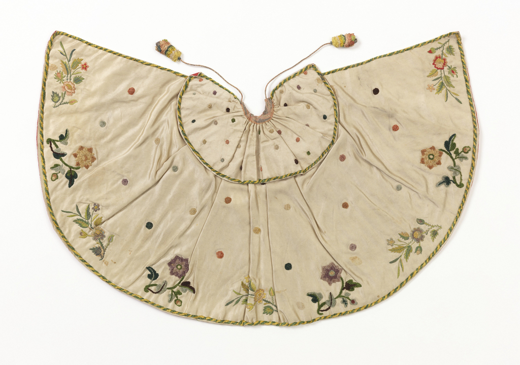 """Small cape for an ecclesiatic figure, the """"Bambino"""". White satin embroidered with silk chenille and silk thread. All-over design of polychrome chenille dots with border design of a single flowering branch alternating chenille and silk. Lined with red taffeta."""