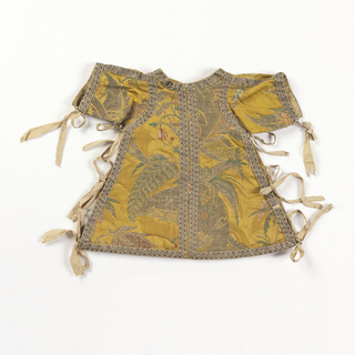 Small tunic of yellow silk satin brocaded in silver metallic threads and polychrome silks. Neck, sleeve and hem edges trimmed with narrow silver ribbon. Open down sides and tied with strips of white silk.