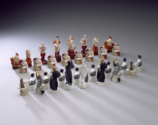 Chess set comprising 32 figures. The red (Communists) set includes: the king as a strapping blacksmith; the queen as a beautiful peasant woman, the bishops as Red Army soldiers, the knights as horse's heads, the rooks as boats with horse head-shaped prows and star-shaped sails, and the pawns as farm workers holding wheat sheafs and sickles. The white (Capitalists) set includes: the king bearing a skeleton face and black robes, the queen holding a cornucopia spilling its gold coins, the bishops as caped and helmeted courtiers, the knights as caparisoned horse's heads, the rooks as swan boats with shield-shaped sails, and pawns as workers bound in chains.