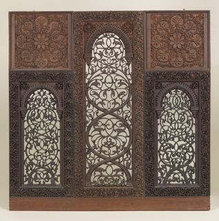 Three carved openwork teak panels with two matching side panels and unique center panel. Side panels are made up of openwork serpentine floral motifts contained within a frame toped with a pointed arch, then surrounded by carved frames made up of sinous vine motifs; top portion is a lighter color wood with framed rosettes. Center panel has carved openwork with serpentine floral motifts contained within a frame topped with a pointed arch and surrounded by frame of sinous vines that takes up the entire height of the piece.