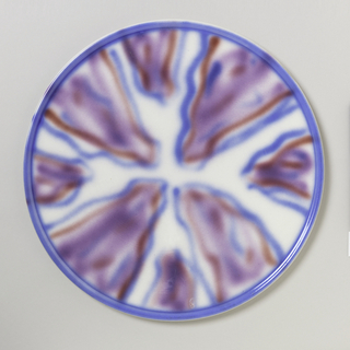 Circular flat plate with slight raised top edge and raised bottom rim.  White ground with solid royal blue top edge.  Blurry tie-dye-like pattern executed over entire surface in muted tones of royal blue, violet, and red.