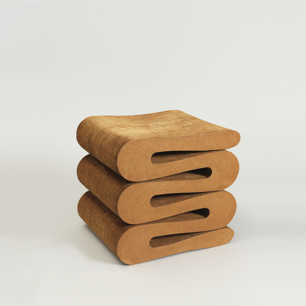 Roughly rectangualr stool made of laminated strips of corrugated cardboard cut to form compressed, repeating upright S-curve; masonite layer on left and right sides; slight contour in surface of seat.
