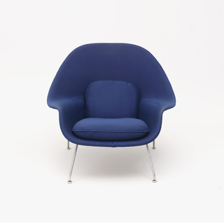 "Blue, open, shell-like chair upholstered in fabric, resting on chrome legs.  The chair's armrests formed by symmetrical ""dips"" in the shell.  Accompanying ottoman, also with chrome legs and a rectangular, blue, cushion."