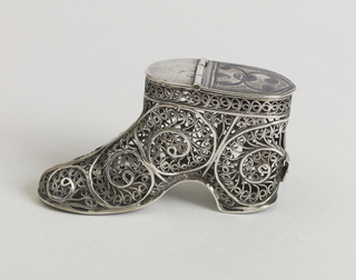 In the shape of a shoe or ankle boot,  the body composed of decorative, scrolling, lacy, filigree motifs,  incised decoration on solid lid at top. Loop at back above heel. Lid hinged at top. Striker on front sole at bottom.