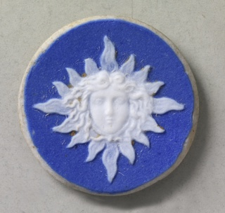 Circular and lozenge shaped medallions or mounts in the style of wedgwood jasperware; ornamented with medusa head, shown full face against rays arranged to for a lognge; whte on blue ground.  Components a,b are on card 4