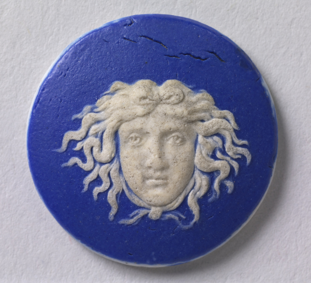 Medallion or mount in the style of Wedgwood Jasperware; ornamented with Medusa head shown full face; white on a blue ground.  In bag, stored with card 4