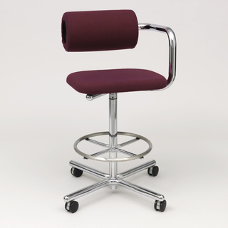 "Swivel stool on four legged rolling base.  Steel foot ring above splayed feet.  Square upholstered seat.  One tubular arm rises at  side, fitted with ""roll"" support; this cylindrical arm or rest is adjustable in height or distance from seat by a ratchet system.  Upholstered in purple hopsack material."