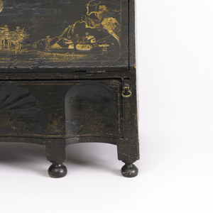 Black and gold lacquered bureau-shaped dressing stand (a/i) on six bun feet, with a long, shaped and carved drawer below a slanted drop-front enclosing an interior fitted with drawers and compartments; two black, turned wood upright supports (j,k) fit into top of stand to hold arched and shaped mirror within a conforming black and gold lacquered frame (l).
