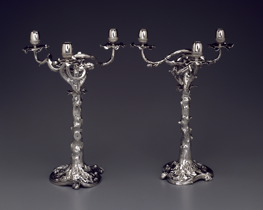 Each three-branched candelabrum in form of an oak tree. Base outlined by three reverse curves; column represents a tree trunk (from which the lower branches have been cut) with leaves at the top and four twisting branches; three of the branches have acorns serving as sockets for candles. The section above the leaves is removable.