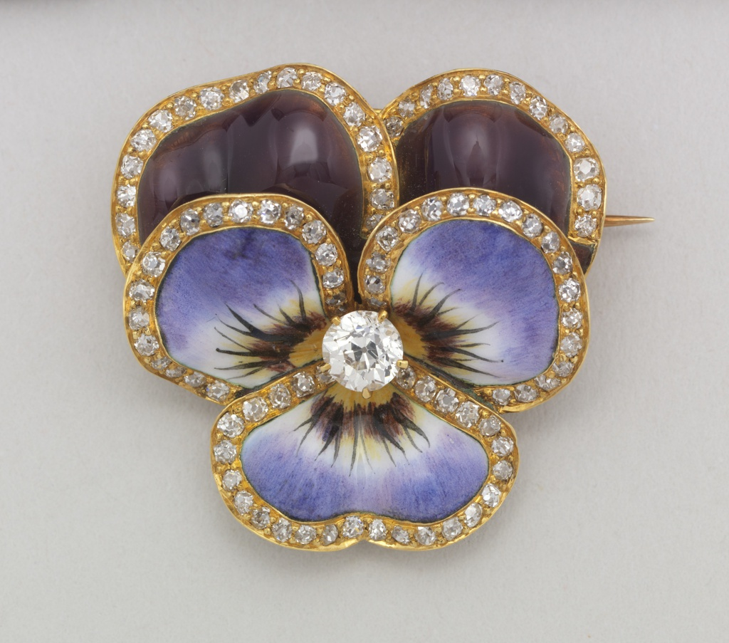 "Enameled gold brooch in the shape of a flower with diamonds along the perimeter of ""petals"" and diamonds in the center."