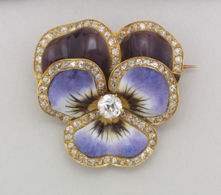 "Enameled gold brooch in the shape of a flower with diamonds along the perimeter of ""petals"" and diamonds in the center. On reverse: gold bar pin and small collapsible ring for hanging as pendant."