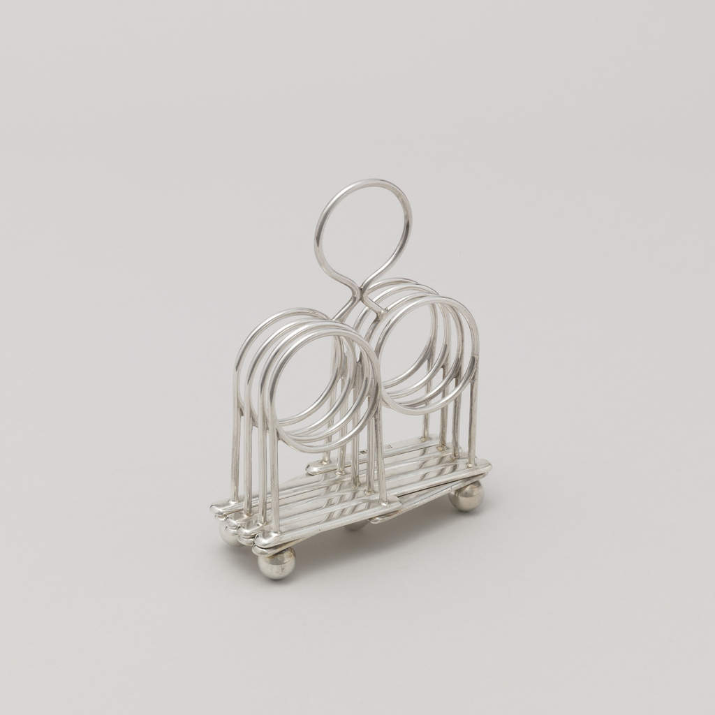 Form consisting of five silver wire partitions looped at the top to form circles, all mounted on a lattice work base, the joints hinged so the rack can be expanded or compressed; supported by five ball feet; raised circular handle on center partition.